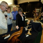 Nila shows her driftwood sculptures to the Rohners